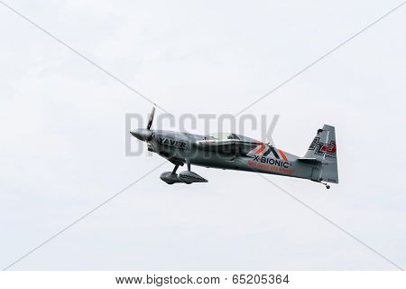 PUTRAJAYA, MALAYSIA - MAY 17, 2014: Hannes Arch from Austria in his Edge 540 V3 plane takes to the skies over Putrajaya lake during the Red Bull Air Race World Championship 2014.