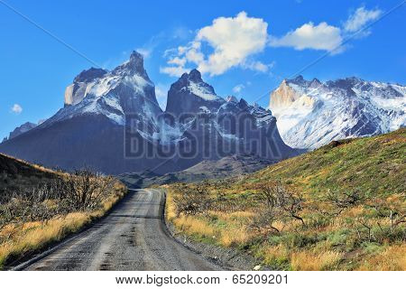 Dreamland Patagonia. Snow-covered cliffs of Los Cuernos, to them is a road of black gravel