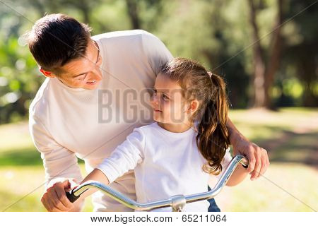 happy young father riding bicycle with his daughter outdoors