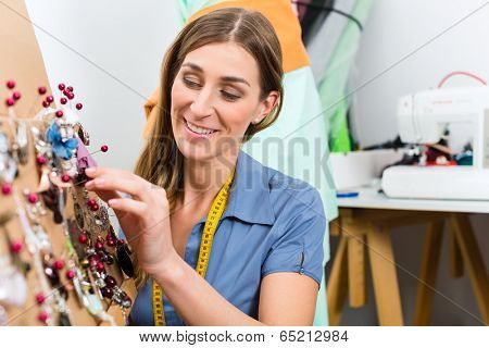 Freelance - jewelry designer working on a draft, different pieces of jewelry hanging in front