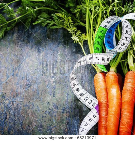 fresh carrots bunch and measurement tape - diet and healthy eating concept