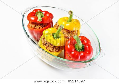 A picture of an unbaked yellow and red stuffed peppers served in a heatproof glass
