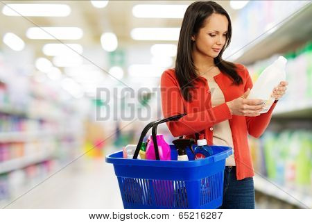 Beautiful brunette woman with basket reading label on cleanser in a shop
