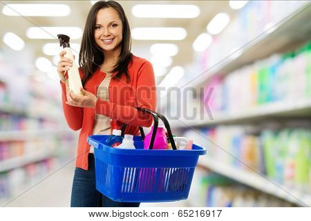 Beautiful cheerful brunette woman with basket full and bottle of cleanser in a shop