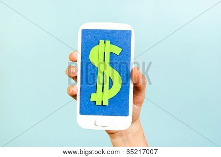 Green dollar money sign symbol mobile phone on blue background. Hand holding a smartphone with sign