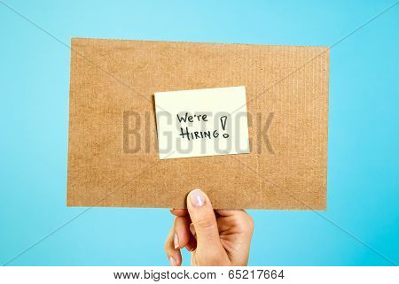 Hand showing We are hiring cardboard on blue background. Job searching concept.
