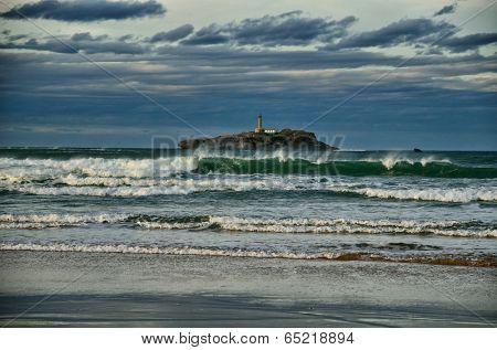 Spanish destination on Atlantic Ocean, Somo beach in Cantabria region, view on lighthouse