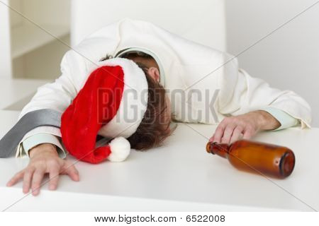 Strongly Drunk Man In Christmas Cap On Table