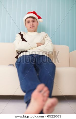 Person In Christmas Cap Sits On Sofa