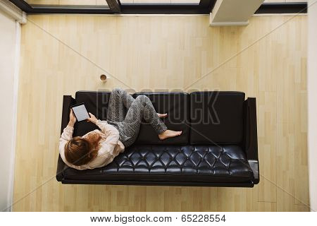 Young Lady Relaxing On A Couch Using Digital Tablet