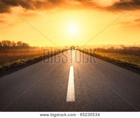 Driving On Asphalt Road Towards The Rising Sun