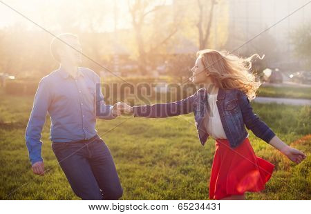loving couple playing in the park at sunset