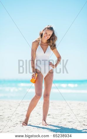 Full Length Portrait Of Happy Young Woman With Sun Block Creme