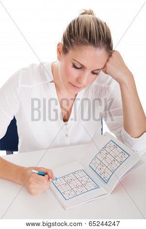 Young Woman Solving Sudoku