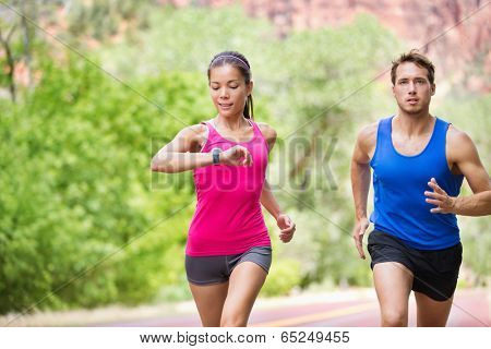 Runners - mixed multicultural couple training outside in nature. Fitness asian young smiling model checking time or pulse on heart rate monitor watch and male model jogging.