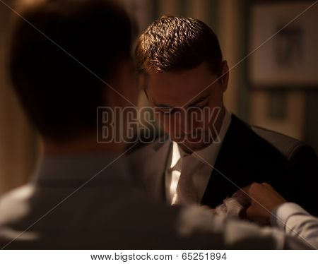 Groomsman fixing boutonniere