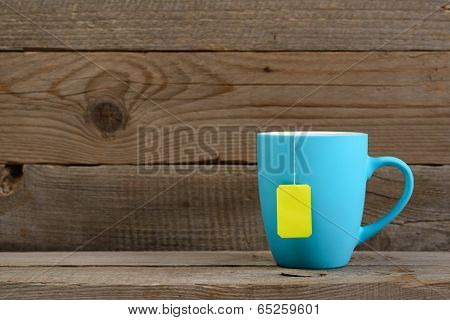 Cup Of Tea With Tea Bag On Old Wooden Background