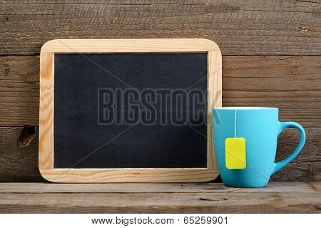 Cup Of Tea And Small Blackboard On Old Wooden Background