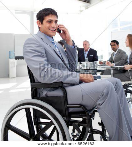 Hombre en silla de ruedas en teléfono durante una reunión de negocios