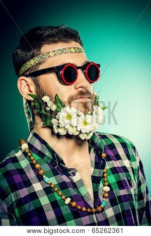 Funny smiling young man in glasses and a beard of flowers. Hippie style.