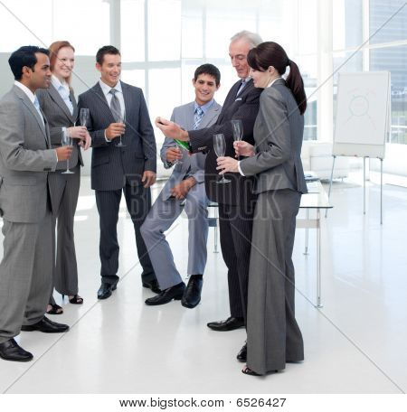Business People Looking At A Bottle Of Champagne