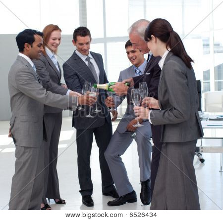 Successful Businessman Serving Champagne To His Colleagues