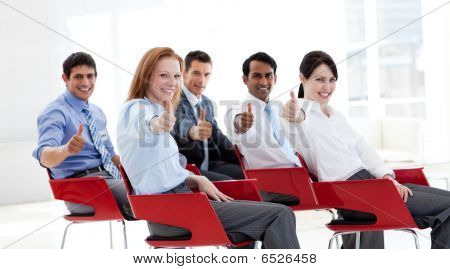 Empresarios con los pulgares para arriba en una conferencia
