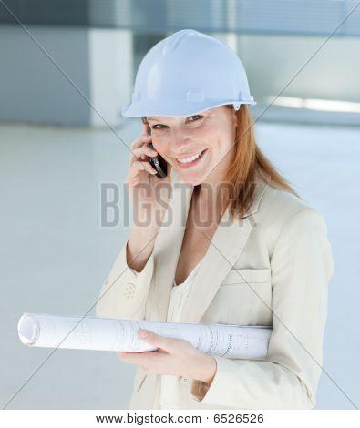 Smiling Female Architect With Hardhat On Phone