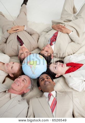 International Business People Lying On The Floor Around A Terrestrial Globe