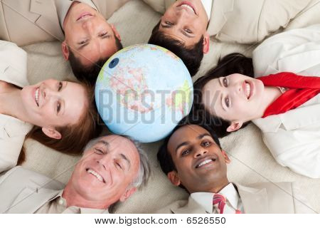 A Diverse Business People Lying On The Floor Around A Globe