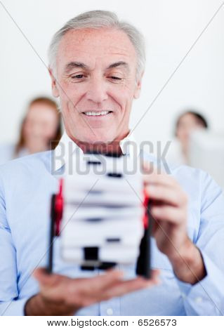 Senior Businessman Holding A Business Card Holder