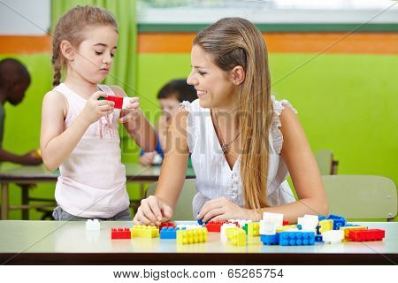 Young woman doing internship in a kindergarten and helping a child