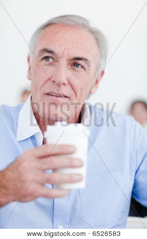 Senior Businessman Holding A Drinking Cup