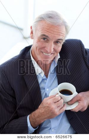 Businessman Drinking And Sitting In A Waiting Room