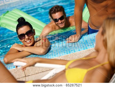 Happy young companionship in swimming pool at summertime having fun.