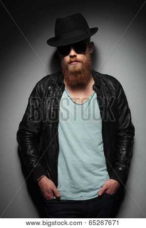 fashion young man with a long beard holding his hands in his pockets and looking into the camera. on a dark studio background