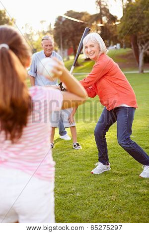 Grandparents Playing Baseball With Grandchildren In Park
