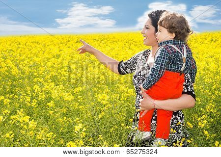 Mom Pointing  To  Rapeseed Field