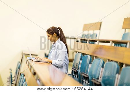indian college student using laptop computer in lecture hall