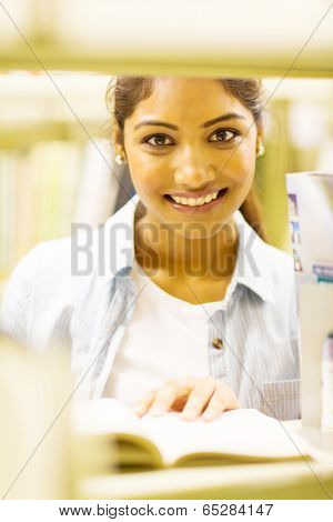 pretty female indian college student reading book in library behind bookshelf