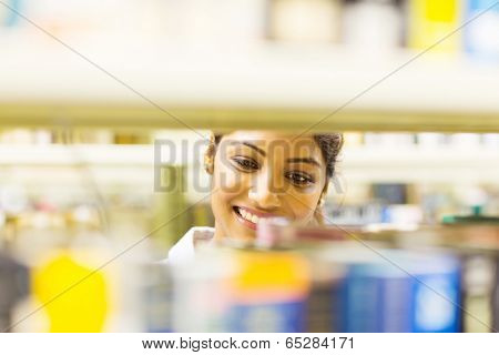 attractive young female college student in library looking for books
