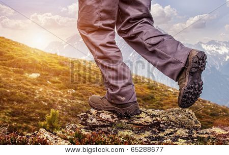Hiker standing on top of a mountain and enjoying sunrise