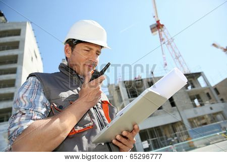 Entrepreneur on building site using tablet