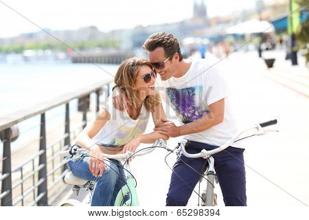 Cheerful couple riding bikes by sunny day