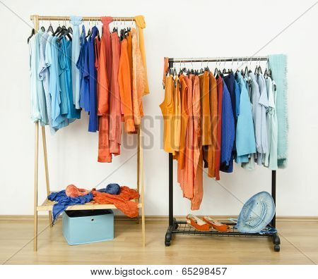 Wardrobe with complementary colors orange and blue clothes on hangers.