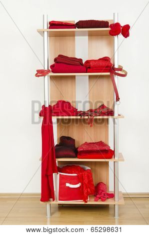 Red clothes nicely arranged on a shelf.