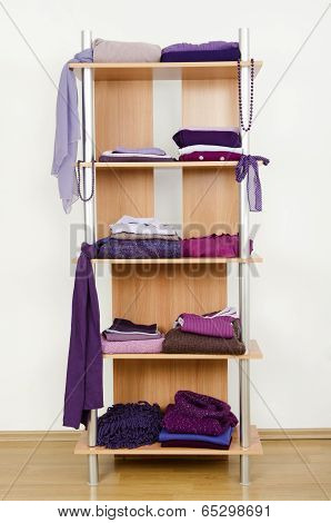 Purple clothes nicely arranged on a shelf.