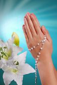 picture of pry  - hands of a girl going to the first holy communion prying with rosary on blue background - JPG