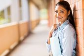 stock photo of indian  - happy indian college student leaning against wall - JPG