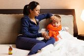 image of high fever  - Young mother and her sick son in a bed - JPG
